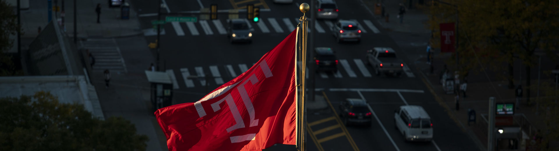 The cherry red Temple T flag flies above North Broad Street